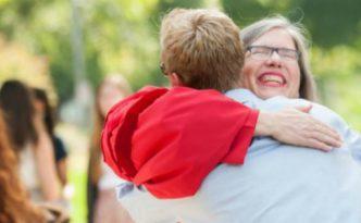 Photo of Judi Biggs Garbuio hugging a student