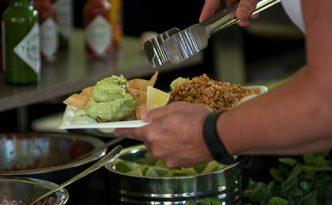 A diner assembles a plate of nachos