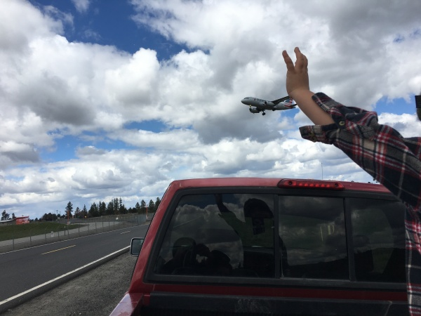 boy watching airplane overhead