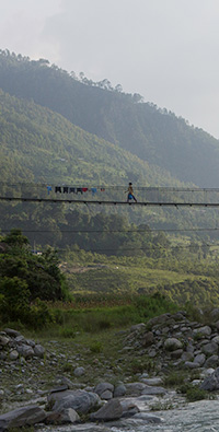 W=A woman crosses a hanging bridge